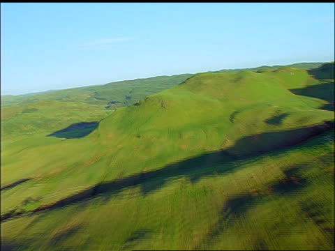 aerial point of view over hill to woman in black dress + hat lying down on top / oban, argyll, scotland - black dress stock videos & royalty-free footage