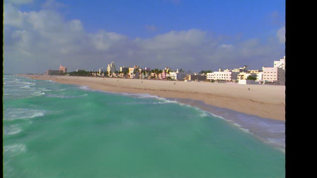 AERIAL point of view over ocean, beach, park + art deco buildings on Ocean Drive / Miami Beach, FL