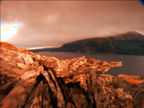 point of view over rocks toward mountain lake with time lapse fog + clouds / glacier natl park, montana / orange filter - glacier national park us stock videos and b-roll footage