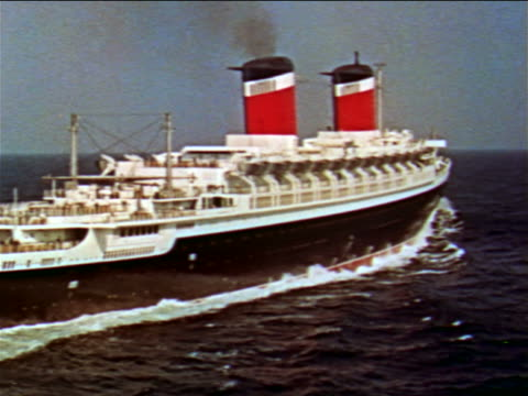 1956 AERIAL point of view past giant ocean liner with 2 red smoke stacks  / S.S. United States / industrial