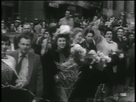 vídeos de stock e filmes b-roll de b/w 1954 point of view past people watching parade throwing streamers after korean war / seattle - 1954