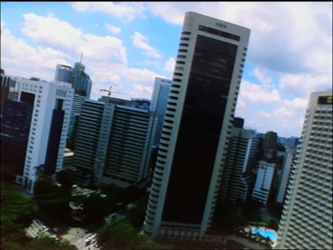 aerial point of view petronas twin towers + skyscrapers / lands by sultan abdul samad bldg / kuala lumpur - sultan abdul samad gebäude stock-videos und b-roll-filmmaterial