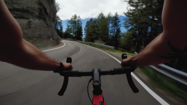 vidéos et rushes de point de vue pov vélo de course sur une route dans la forêt des dolomites - caméra portable