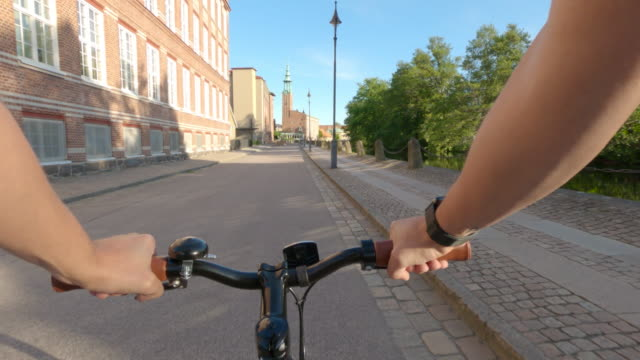 stockvideo's en b-roll-footage met standpunt dat een fiets door de stad berijdt - sunny