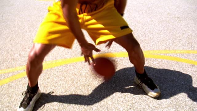 vídeos de stock e filmes b-roll de ms shaky point of view shirtless black man dribbling basketball around camera on outdoor court / los angeles - super exposto