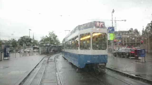 point of view shot filmed from the rear of a tram carriage during journey along city streets between station stops on a rainy day in zurich... - tram point of view stock videos and b-roll footage