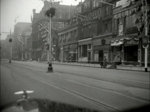 vidéos et rushes de point of view shot from the front of a car moving along a quiet princes street on the morning of the queen's state visit to scotland 1953 - car point of view