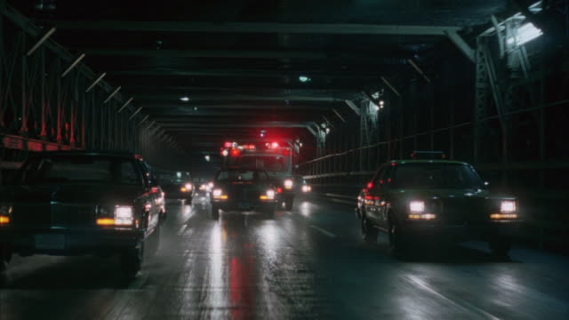 Point of view shot of an ambulance maneuvering  through heavy traffic on a bridge.