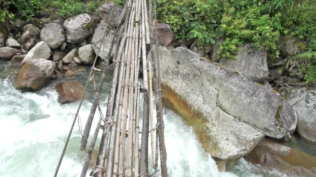A point of view shot of someone walking across a narrow footbridge in the remote jungle of Khakaborazi National Park