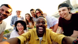 Point of view shot of young people multiethnic group taking selfie and holding camera, men and women are looking at camera, smiling and posing with drinks at rooftop party.