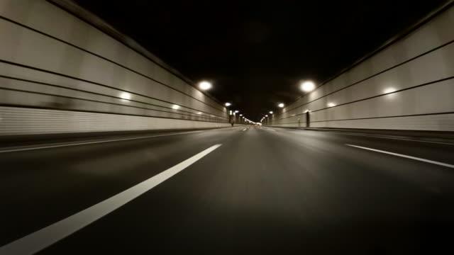vidéos et rushes de point de vue tiré sur le tunnel de l'autoroute de la ville. conduite sur les routes urbaines à travers la circulation urbaine au crépuscule. - vue latérale