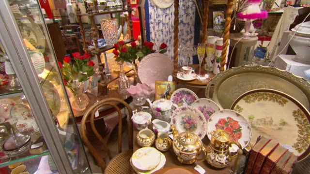 point of view shots walking through large vintage wares antiques shop warehouse including crockery pictures clothes furniture and bric a brac - ブラック島点の映像素材/bロール