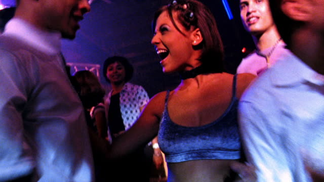 point of view thru crowd dancing in nightclub to young woman dancing toward young man, hugging + kissing him - clubs besuchen stock-videos und b-roll-filmmaterial