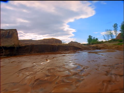 point of view time lapse clouds over wet muddy landscape with rock formations in background / canyonlands national park, utah - canyonlands national park stock videos & royalty-free footage