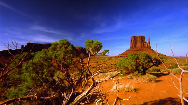 point of view time lapse over desert plants + floor with butte in distance / monument valley, usa - butte rocky outcrop stock videos & royalty-free footage
