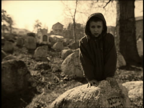 b/w ms point of view toward boy leaning on gravestone in jewish cemetery / sarajevo, bosnia-herzegovina - one boy only stock videos and b-roll footage
