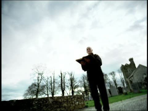 high contrast shaky point of view toward senior man reading from book on country road / church in background / ireland - 薄毛点の映像素材/bロール