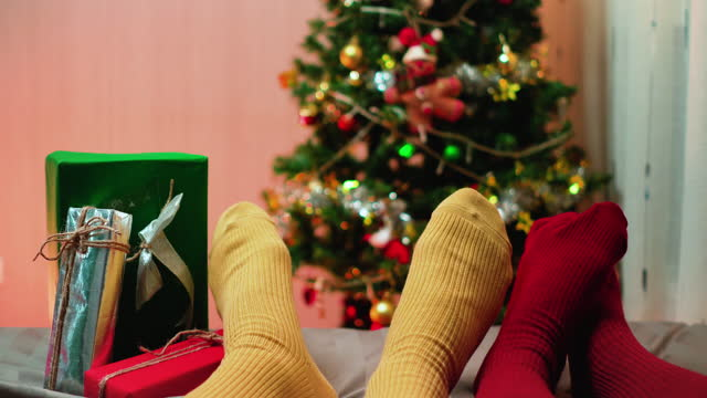 point of view:  two pairs of christmas socks, a southeast couple laying down on the bed, and wearing red and yellow socks against christmas tree with ornament and light and playing with feeling happiness together at night. - sock stock videos & royalty-free footage