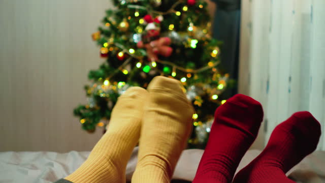 point of view:  two pairs of christmas socks, a southeast couple laying down on the bed, and wearing red and yellow socks against christmas tree with ornament and light and playing, dancing music with feeling happiness together at night. - sock stock videos & royalty-free footage