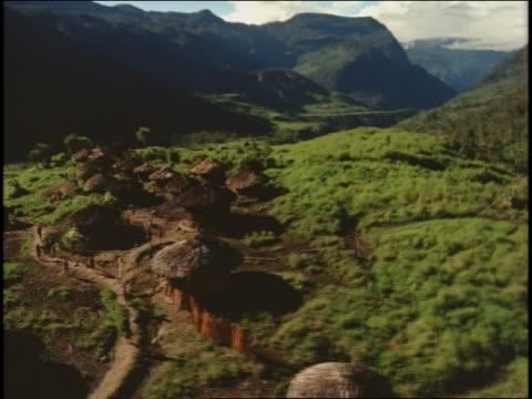 vídeos y material grabado en eventos de stock de aerial point of view village of grass huts in the mountains - cabaña de paja