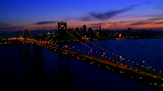 vídeos y material grabado en eventos de stock de aerial point of view wide shot bay bridge towards skyline + over city at dusk / san francisco, california - pirámide transamerica san francisco