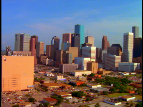aerial point of view wide shot over city streets + skyscrapers of downtown houston, texas - 1996 video stock e b–roll