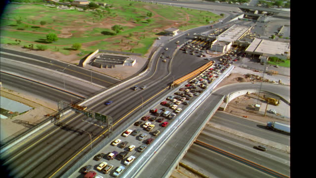 AERIAL point of view wide shot over highways with heavy traffic at US/Mexico customs border station / Texas