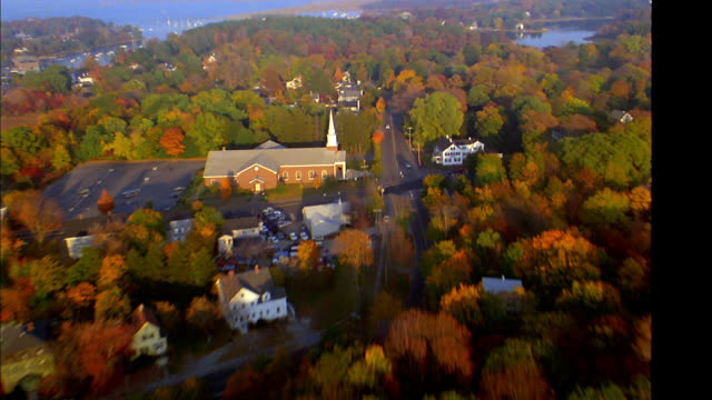 AERIAL point of view wide shot over town, harbor, rivers, trees + farmland in autumn / Massachusetts