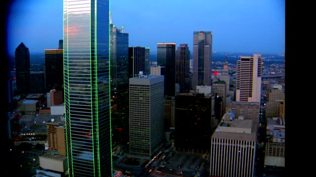 AERIAL point of view wide shot past skyscrapers at twilight with Bank of America Plaza in foreground / Dallas, TX