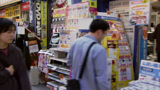 point of view wide shot walking past electronics stores and pedestrians on sidwealk in akihabara district / tokyo - akihabara stock videos and b-roll footage