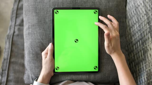 synvinkel kvinna söker och använder på digital tablet green screen - över axel perspektiv bildbanksvideor och videomaterial från bakom kulisserna