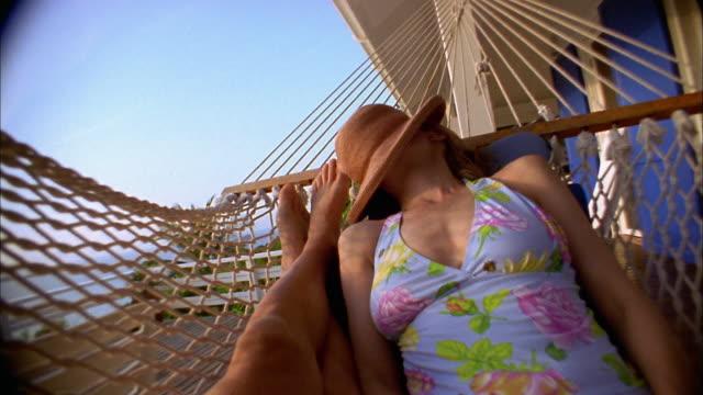 vídeos de stock e filmes b-roll de point of view woman swinging in hammock with hat over face / man's legs - cama de rede