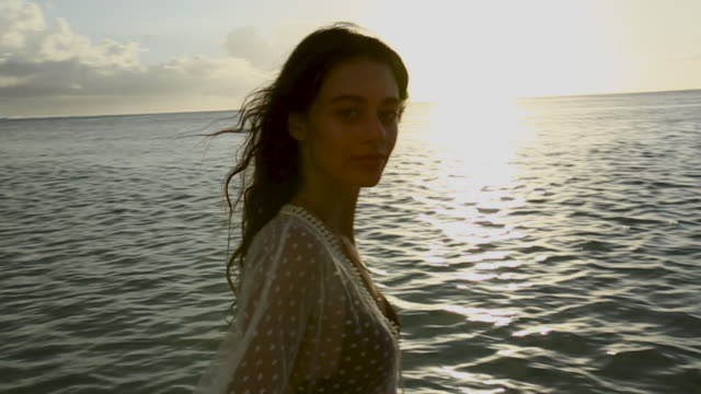 vidéos et rushes de point of view, woman wades in water in tahiti at sunset - maillot de bain