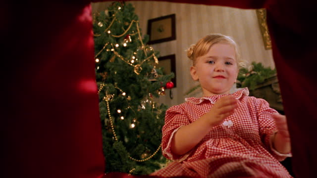 point of view young girl opening present and smiling with christmas tree in background - gift stock videos and b-roll footage