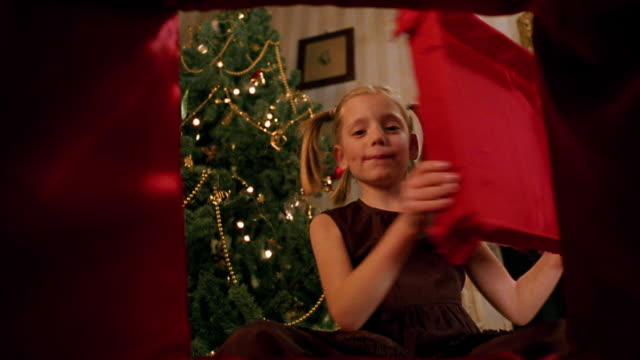 vidéos et rushes de point of view young girl opening present and smiling with christmas tree in background - cadeau