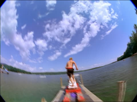 stockvideo's en b-roll-footage met fisheye rear view point of view young man running down dock + jumping in weird pose off diving board into lake - steiger pier