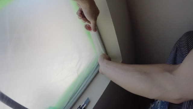Point of view,Man preparing to paint by taping window