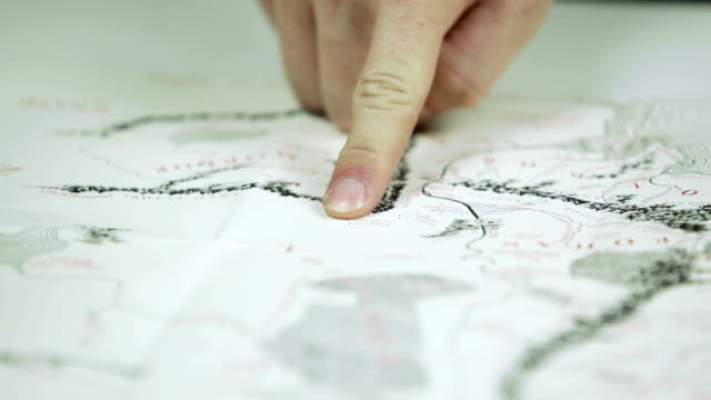 pointing with finger on a treasure map - cartography stock videos & royalty-free footage