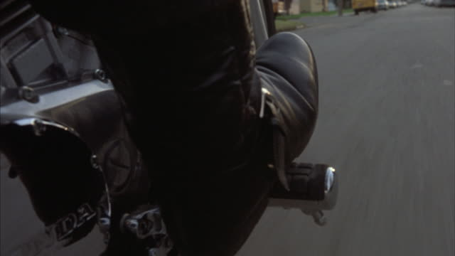 Point-of-view of a booted foot on a motorcycle footrest.