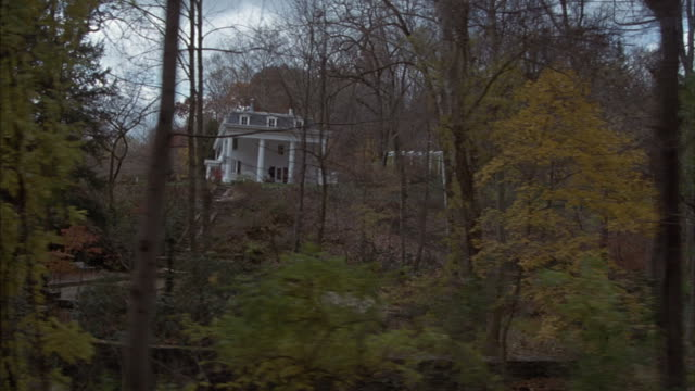 Point-of-view of slowly driving past stately homes in an affluent neighborhood.
