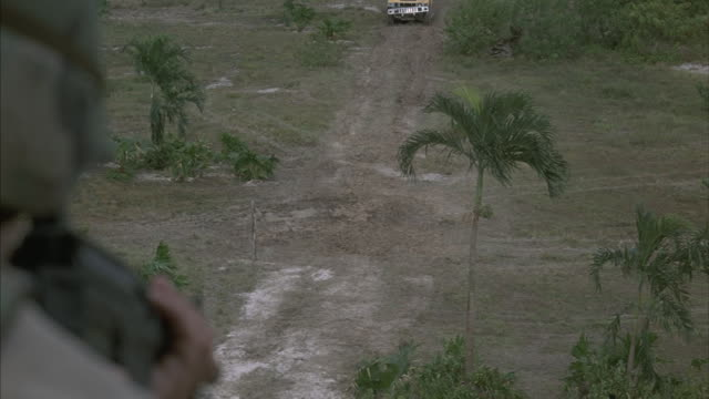 point-of-view shot as a sentry takes aim and fires at a speeding hummer and land-rover below as they crash through barricade and come to a stop. - autoperspektive stock-videos und b-roll-filmmaterial
