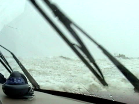 Point-of-view shot from inside car getting picked up and moved by powerful storm surge during hurricane.