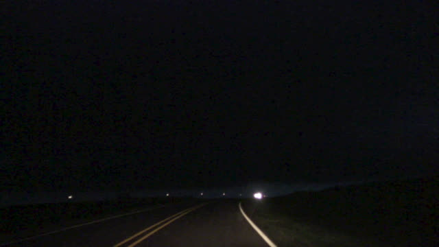 Point-of-view shot from inside moving car of lightning striking close-by during the night.