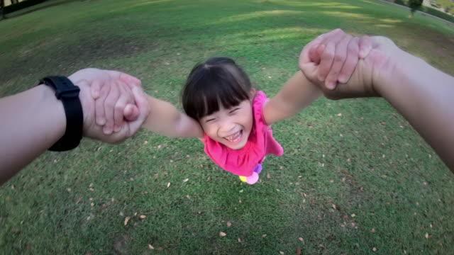 回転カメラで子供を浮かべて、公園での周り彼の若い娘の父の視点のショット - 子供点の映像素材/bロール