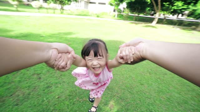vídeos y material grabado en eventos de stock de punto de vista de la toma de un padre dando vueltas alrededor de su joven hija en el parque, niños sonriendo a la cámara - eufórico