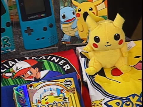 pokemon merchandise ranging from game boy cartridges to trading cards and other collectibles are displayed on a table. - pokémon stock videos & royalty-free footage