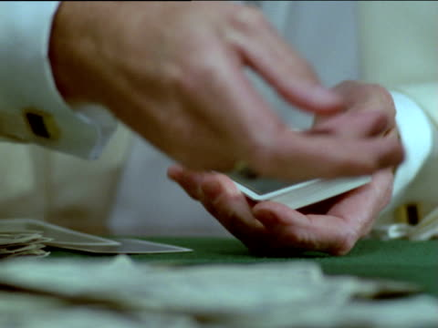 poker dealer distributes playing cards across table littered with bank notes - カードゲーム点の映像素材/bロール