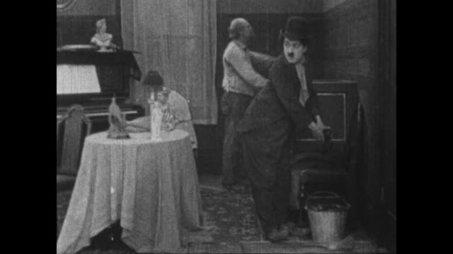 1915 Poker faced Charlie Chaplin deliberately soils boss's clothes as he helps him change