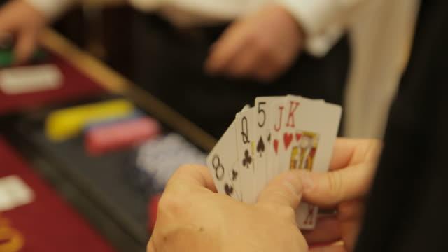 vídeos de stock, filmes e b-roll de segurando cartas de poker - texas hold 'em
