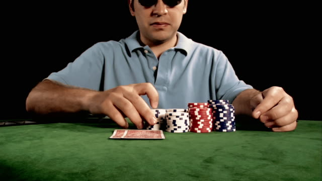 poker player looking at hand / going all in by stacking chips in front of camera / crossing arms on top of table - poker stock-videos und b-roll-filmmaterial